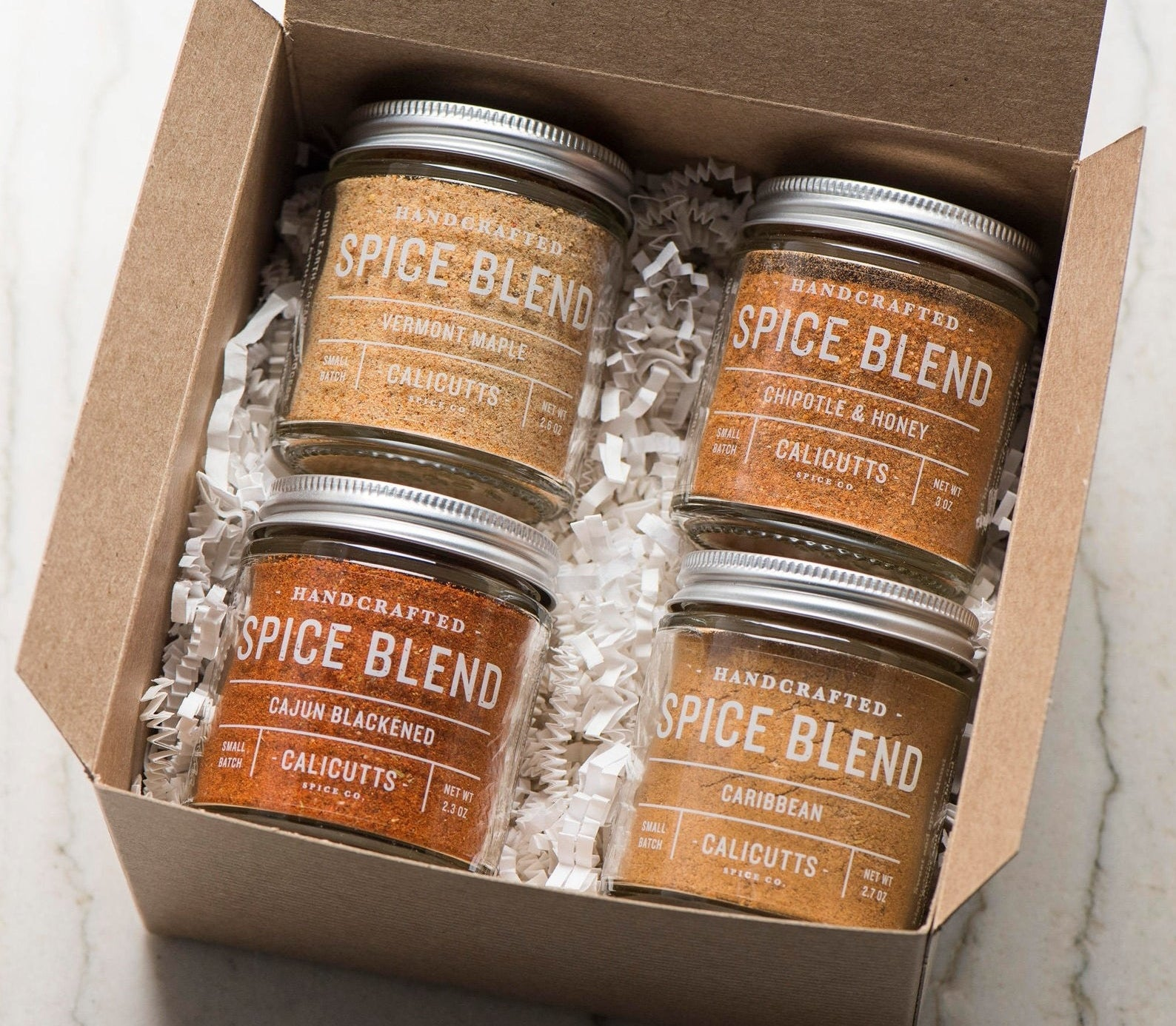 the four jars of spices that come in the pack — vermont maple, chipotle and honey, cajun blackened, and caribbean