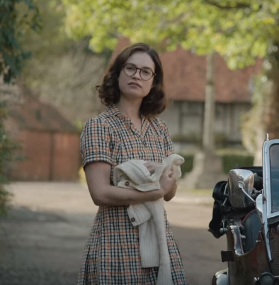 Still from The Dig: Peggy holding cardigan in plaid dress