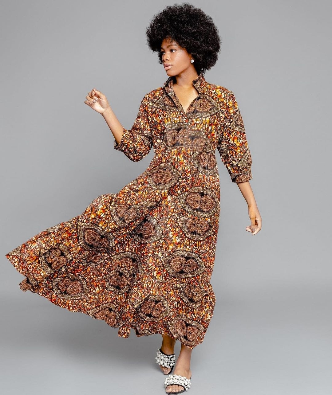 model wearing a vibrant paisley patterned dress with a v-neck and collar