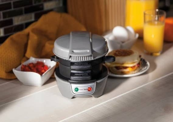 The sandwich maker shown on a kitchen counter with breakfast foods