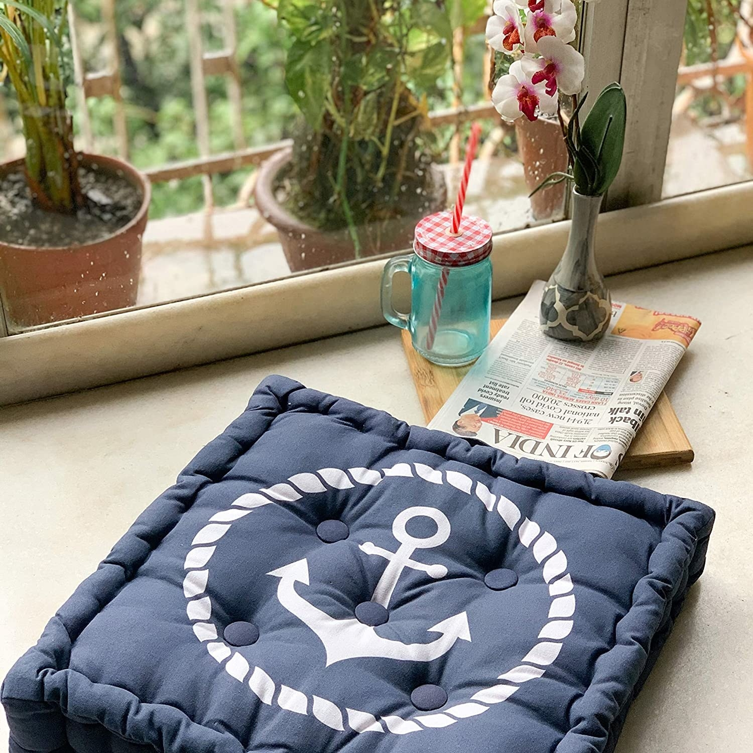 A navy floor pillow with an anchor on it