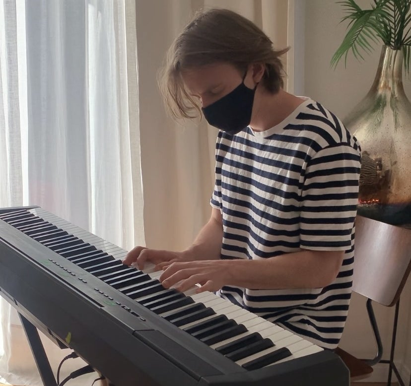 Stephen plays piano with a mask on