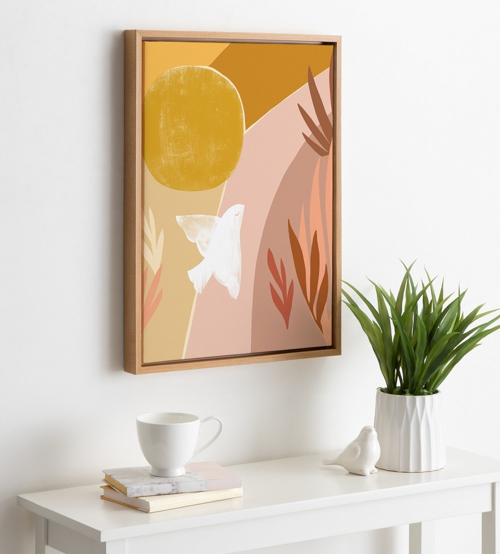 The framed art hung on a white wall