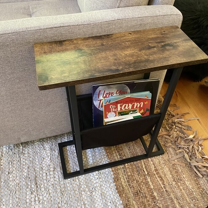 side table with a wooden top and a black bottom with a magazine holder