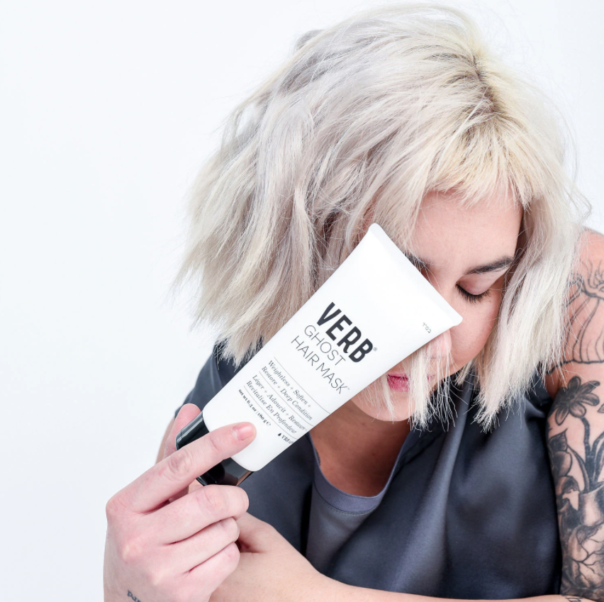 model with bleached hair holding tube of hair mask