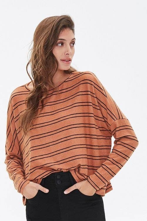 Model wears orange and black striped top with black jeans