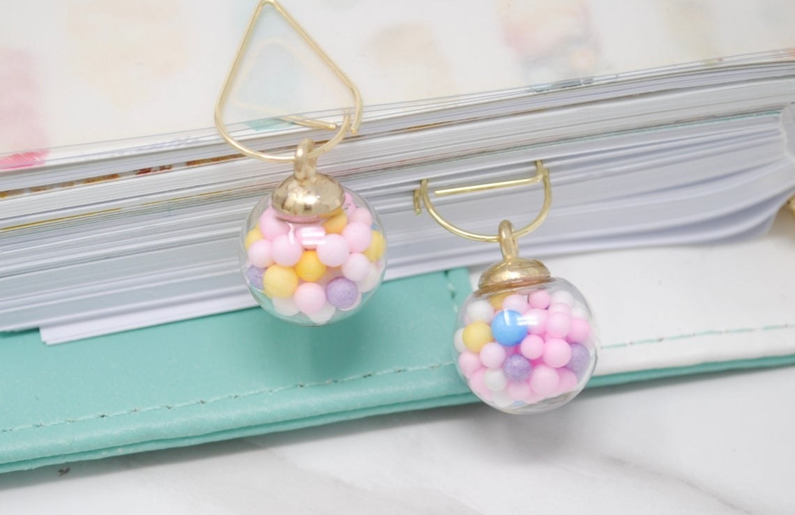 paperclips with round glass charms filled with colorful balls