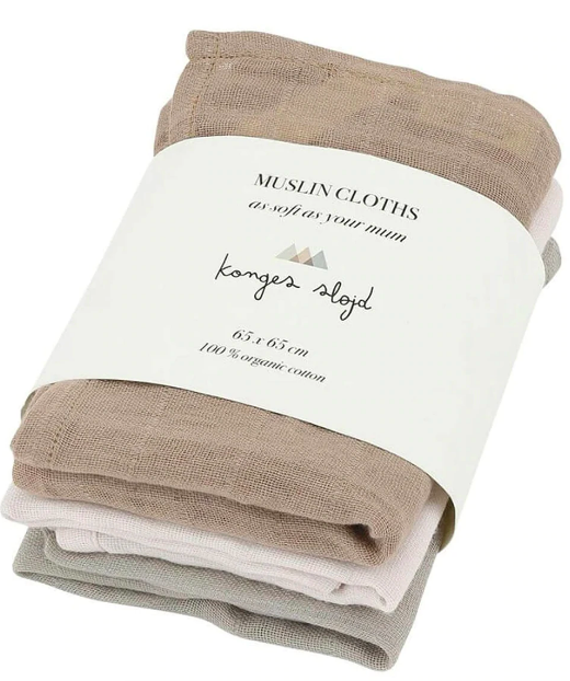 Three burp clothes in natural colors folded together in minimalist packaging