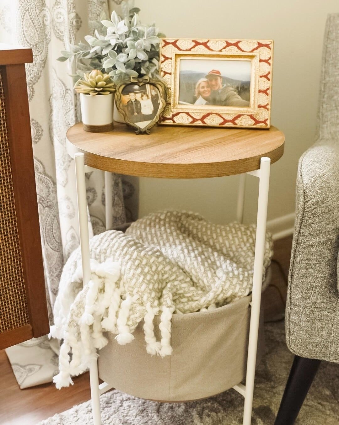 reviewer pic of the round side table with wood top, grey fabric basket at the bottom and white legs
