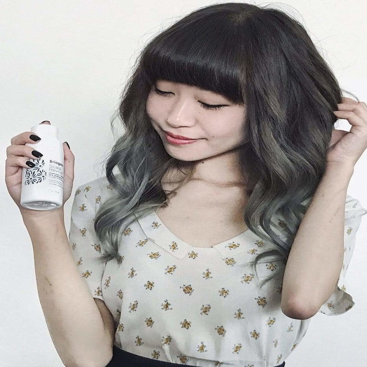 A model with dark hair holding a bottle of Scalp Revival Charcoal and Biotin Dry Shampoo