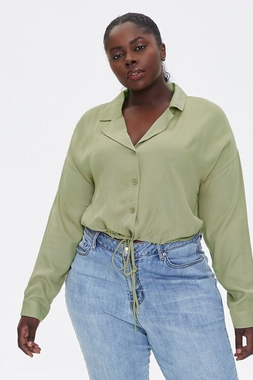 Model wears the olive green drawstring-hem top with light wash jeans