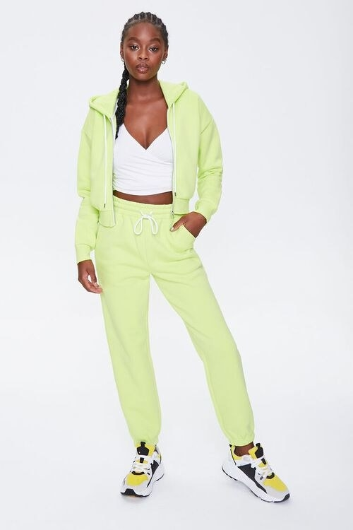 Model wears lime joggers with matching jacket and black and yellow sneakers
