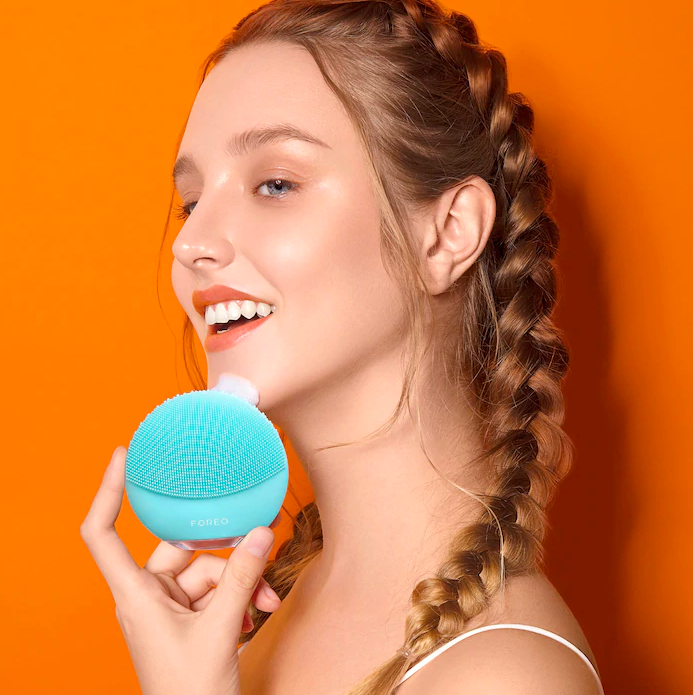 A person holding an electric silicone sponge to their face