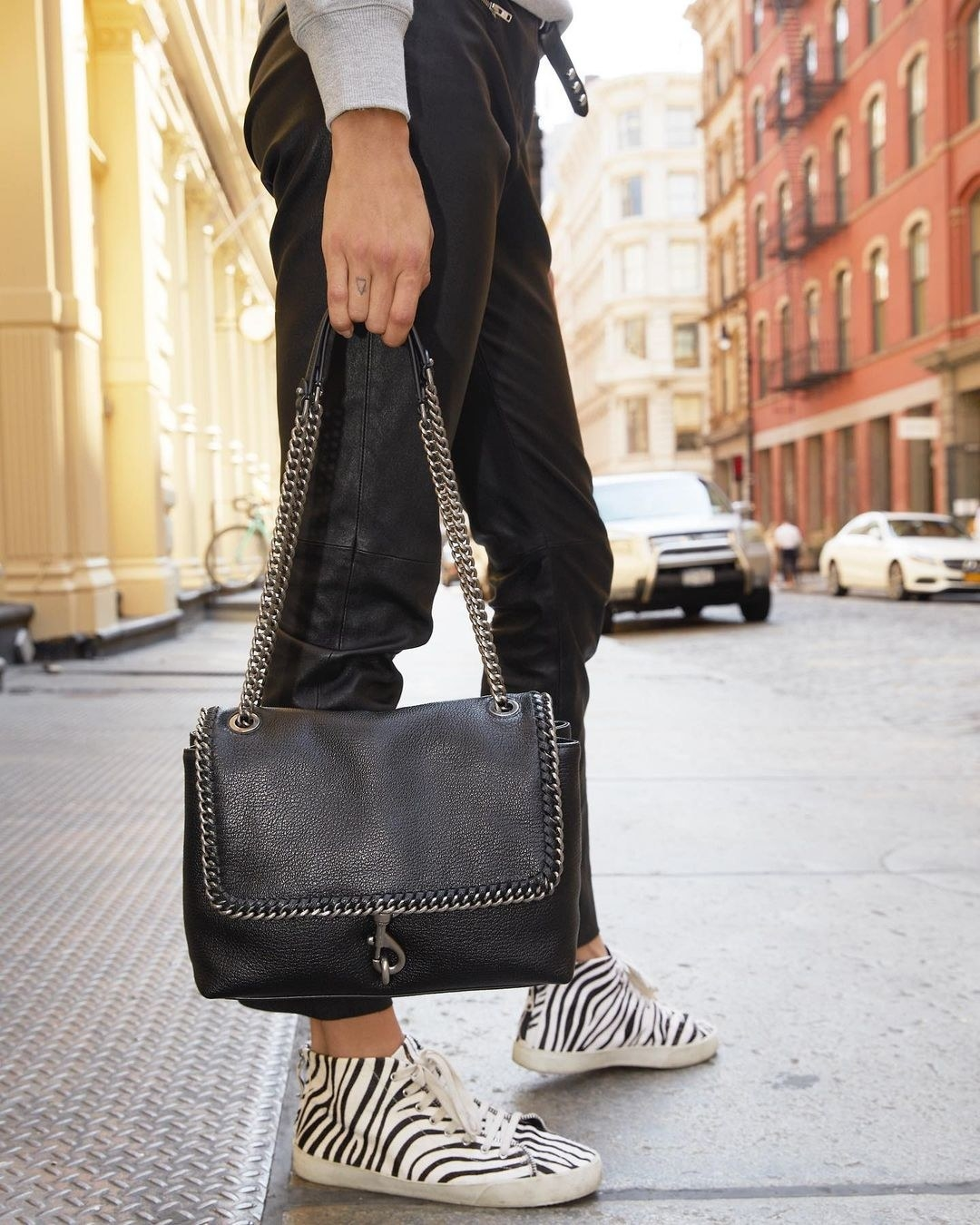 a model holding a leather bag with chain detailing