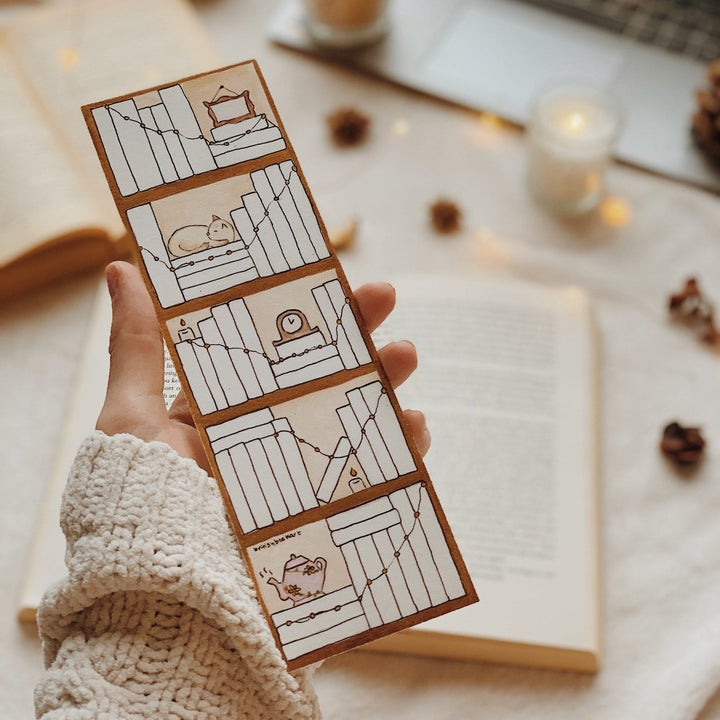 person holding the bookmark before it's filled in/colored with books read