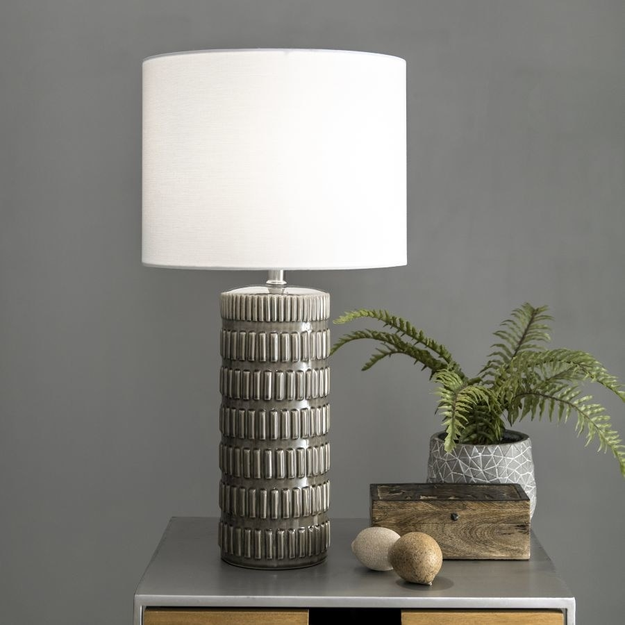 Grey tubular lamp with textured lines all over it and a white lampshade