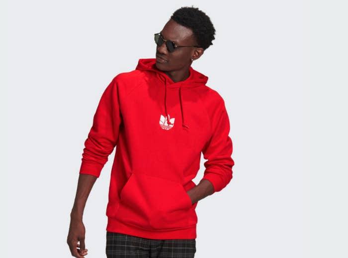 Model wearing a red Adidas hooded sweatshirt