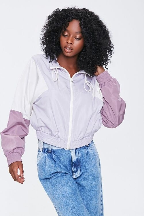 Model wears cream and purple multi colorblock windbreaker with midwash jeans