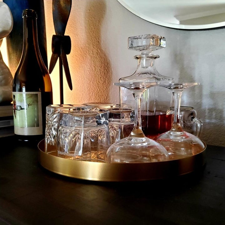 A reviewer using the gold tray to hold glasses and liquor bottles