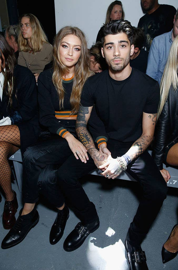 Gigi and Zayn sitting next to each other at the front show of a fashion show