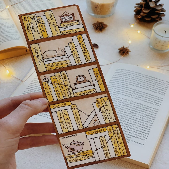 person holding the bookmark after coloring it and writing in the name of finished books