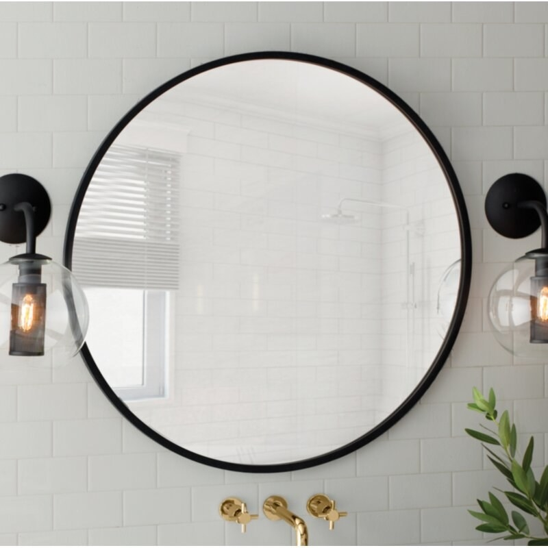 round mirror with black edges hung on a tiled wall