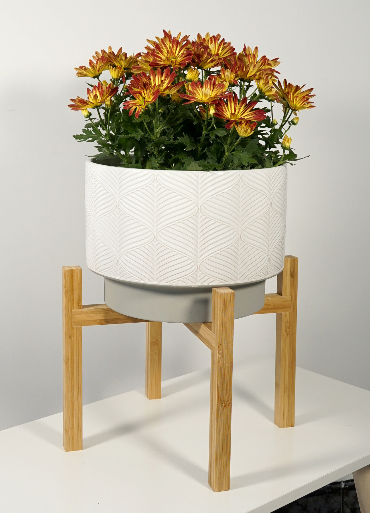 a ceramic planter with white and grey designs with a grey base on a wooden stand