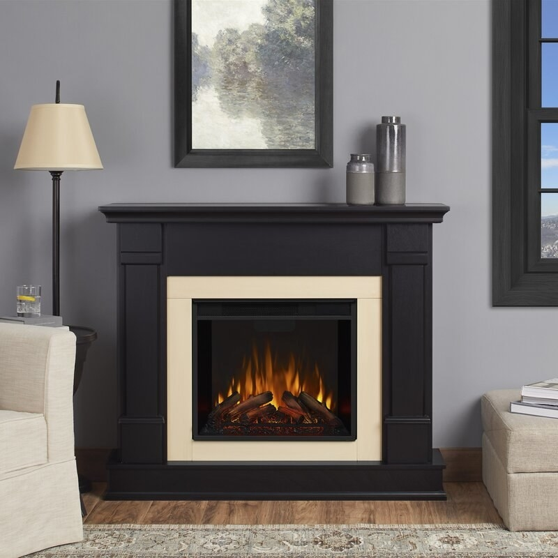 "the square fireplace with mantle in black with electric ""fire"" in the middle"