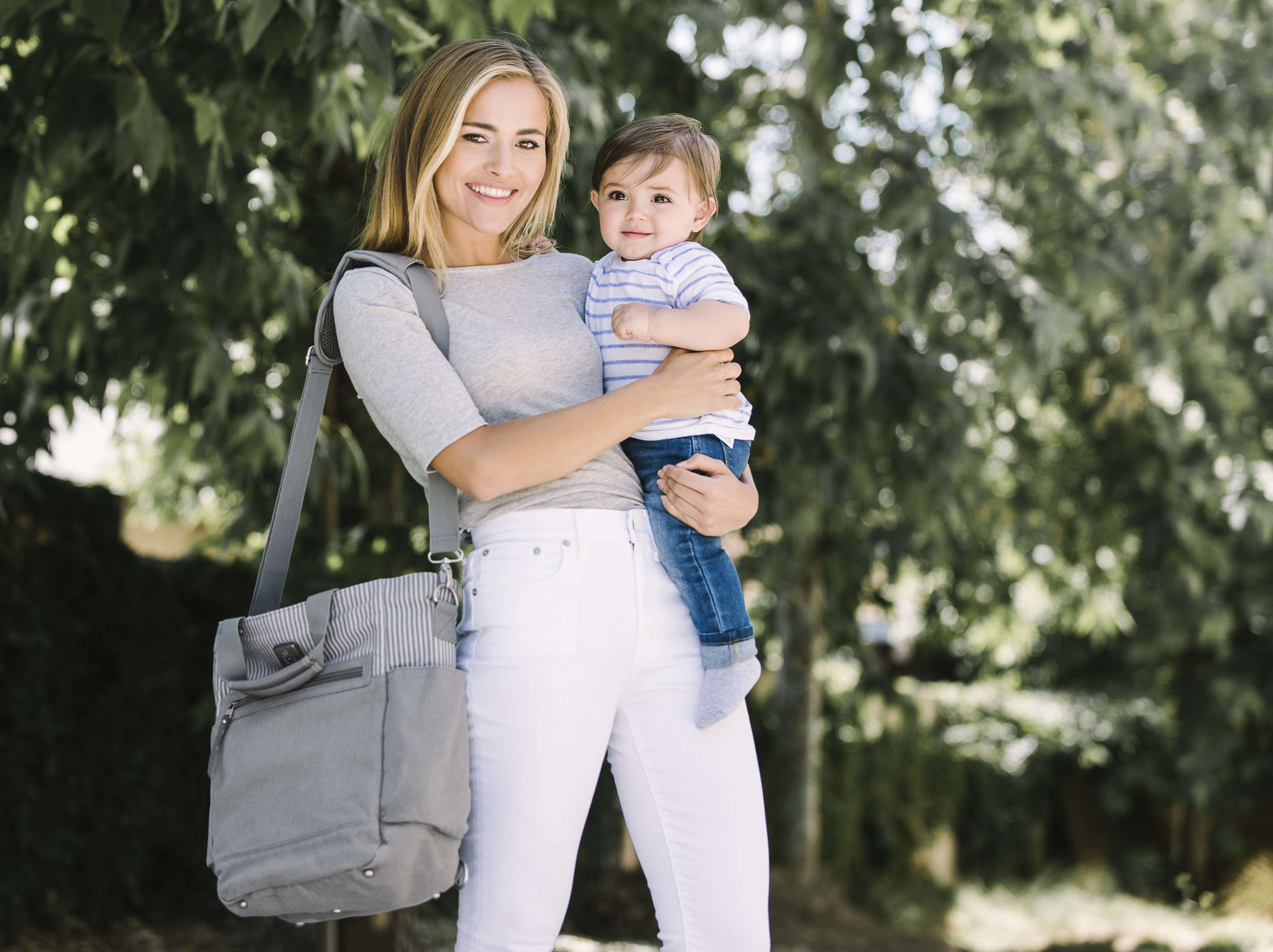 model with a gray diaper bag tote bag on the shoulder and also holding a baby