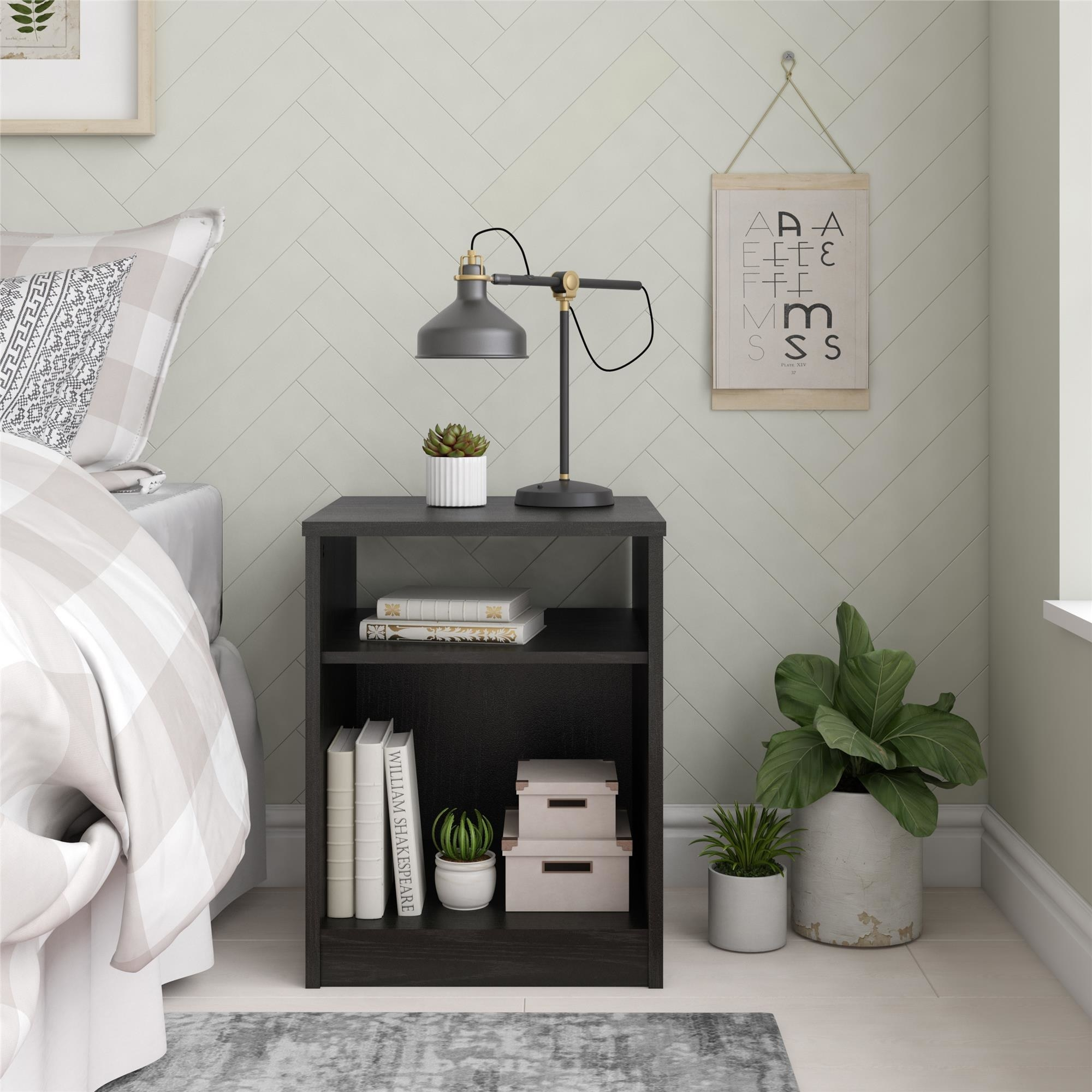 a black open shelf night stand with books and boxes on its two shelves, and a lamp and plant on its top