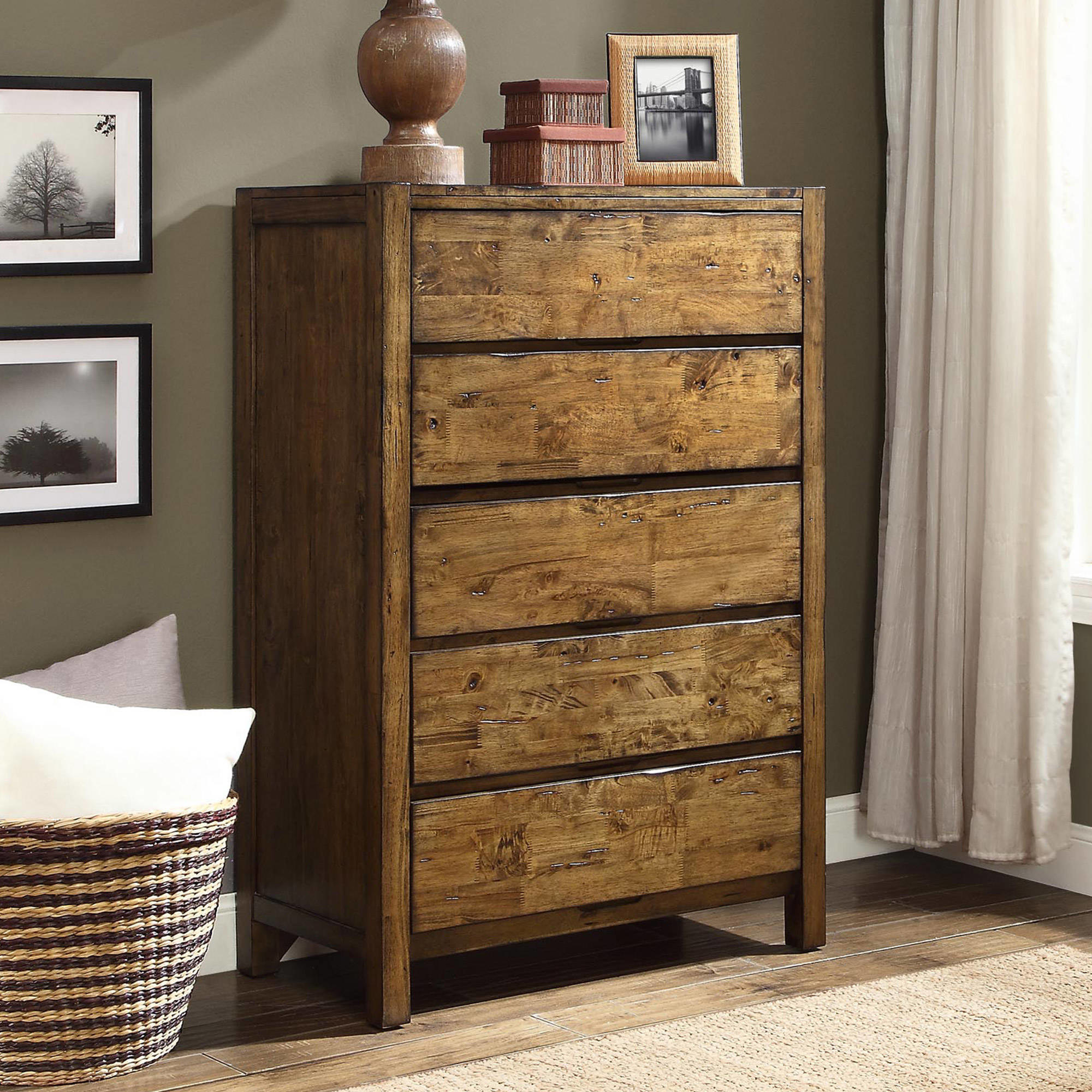 a rustic wooden tall dresser with five drawers, with decor resting on top of it