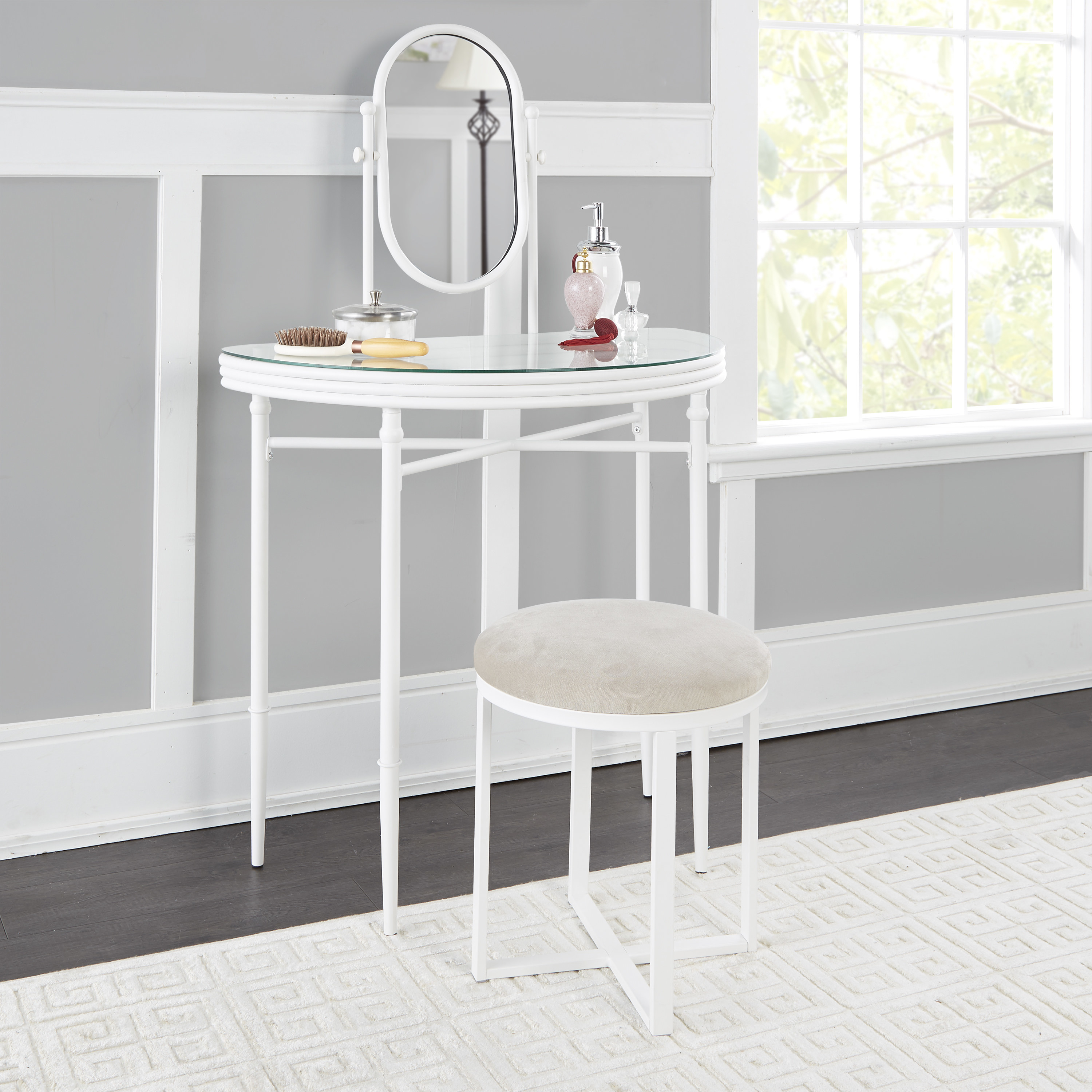 a white metal vanity with a glass top, an oval mirror, and a white metal cushioned stool