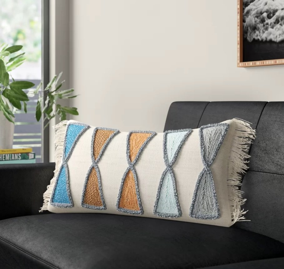 Ivory colored lumbar pillow with fringed sides and geometric blue, orange and gray geometric detailing