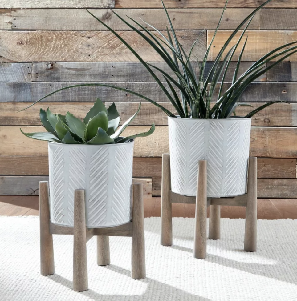 two wooden stands holding white, round planters with diagonal etching in them