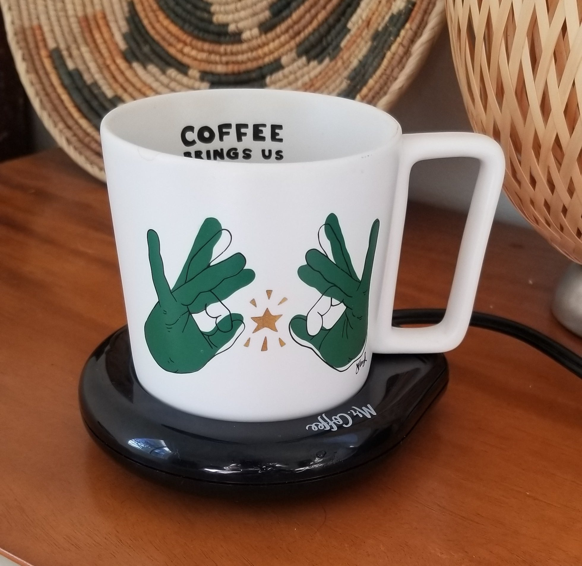 The mug warmer on a bedside table with mug on top