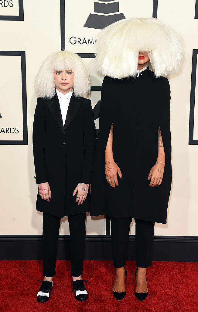 Sia and Maddie posing in matching suits and wigs on the Grammys red carpet