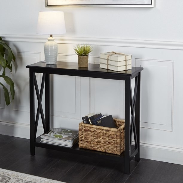 black wooden console table with accessories on it
