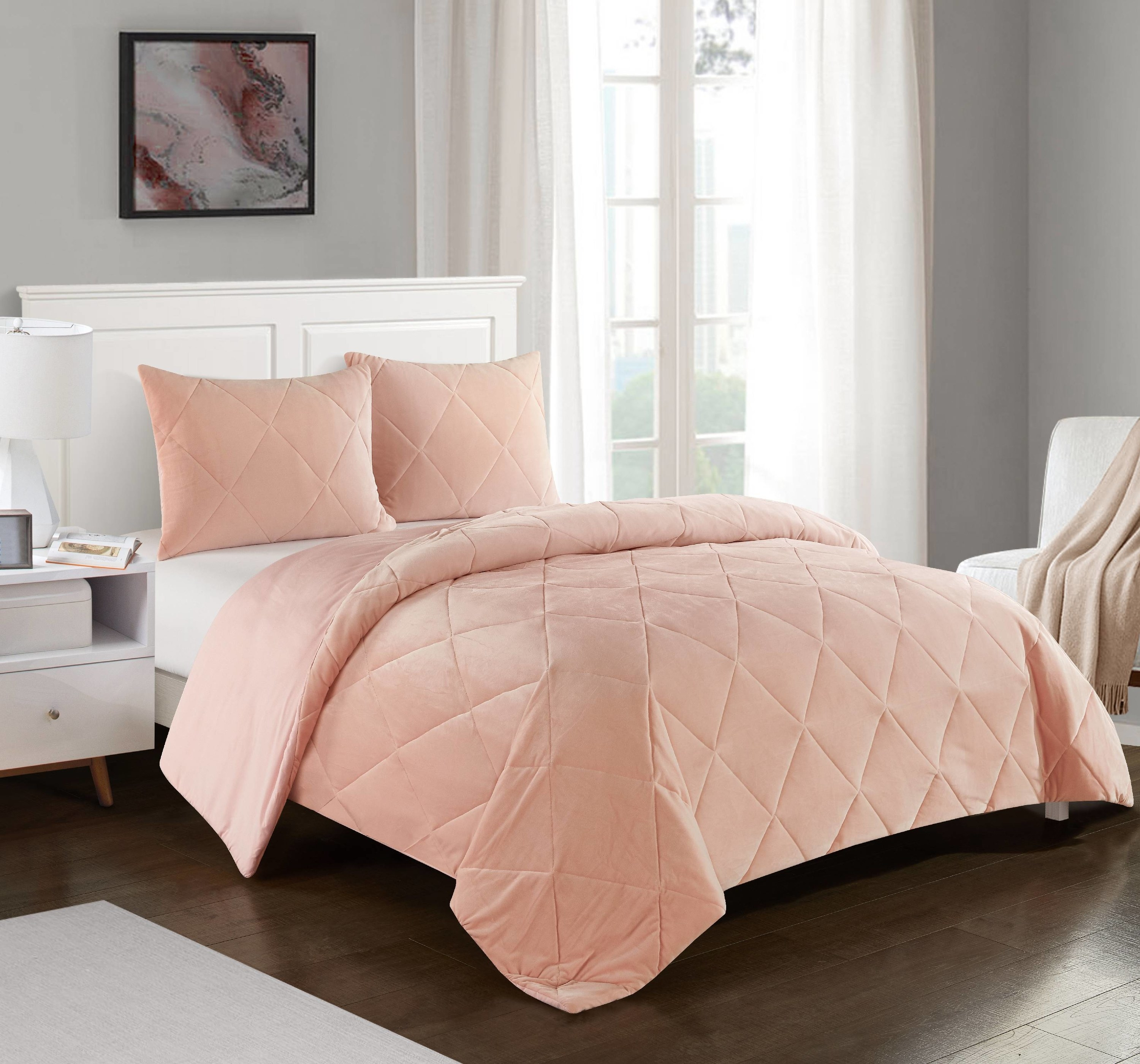 pink comforter and shams on a bed