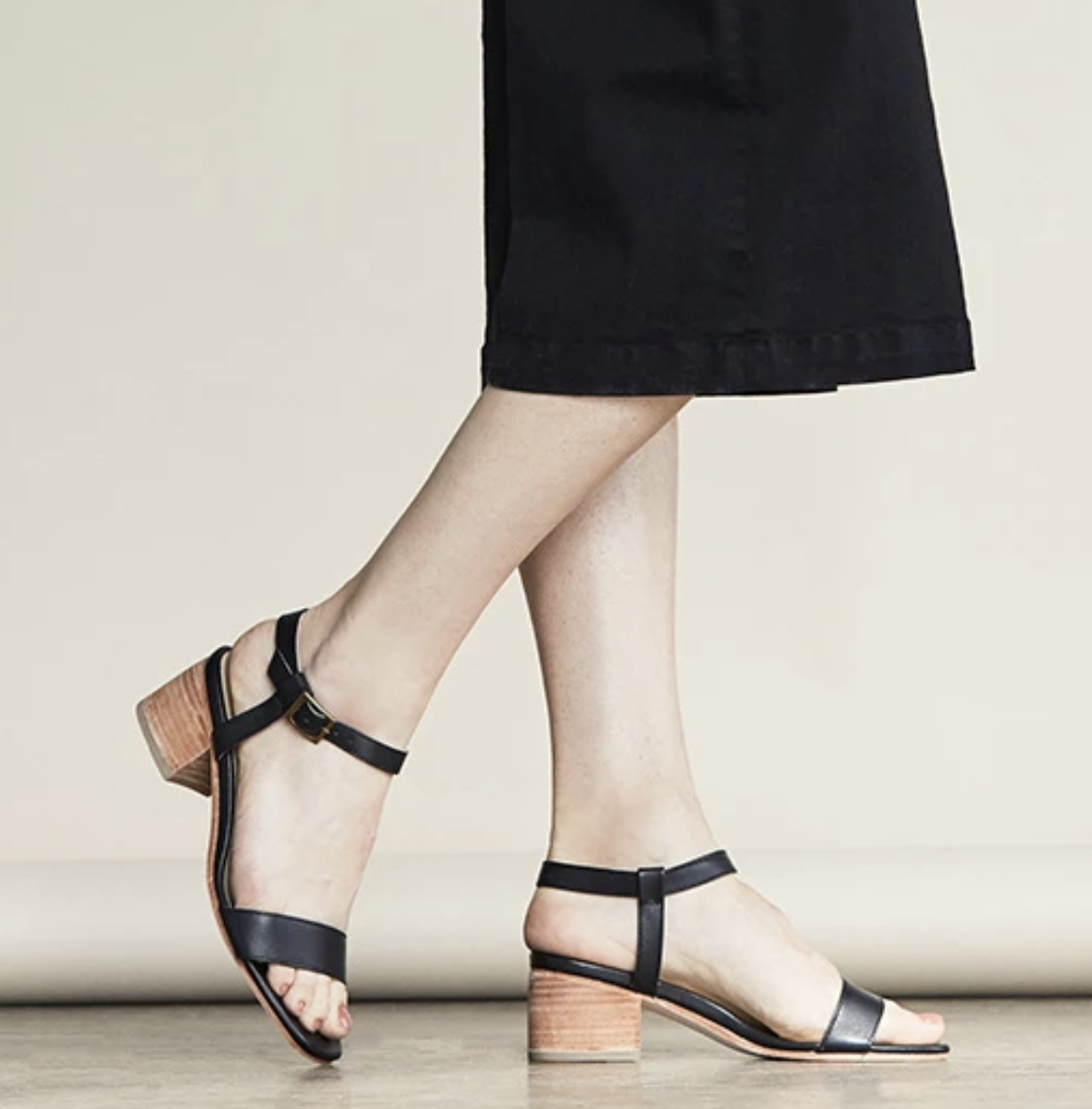 Model in black heeled strappy sandals with light wood inspired heel