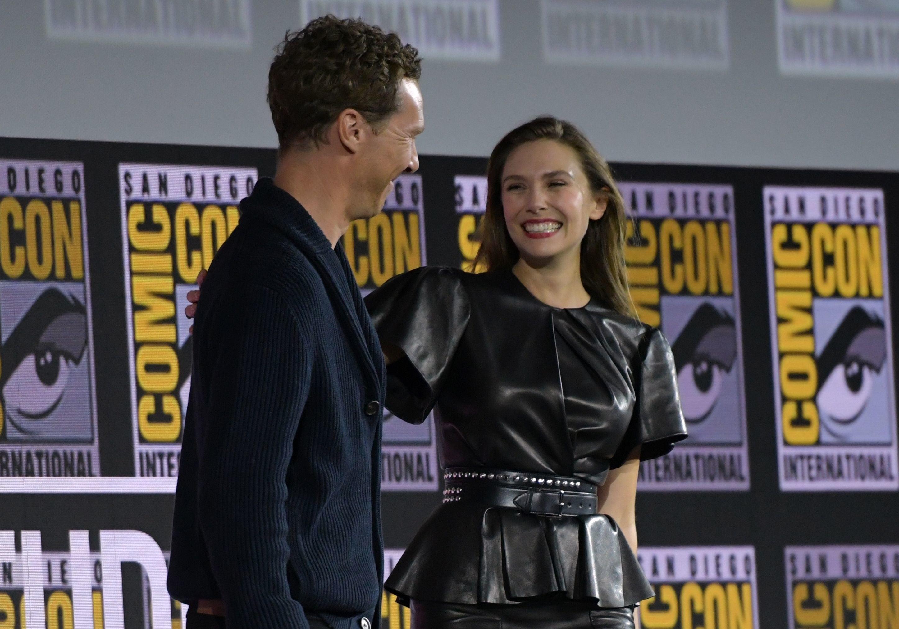Elizabeth Olsen smiling at Benedict Cumberbatch, who plays Dr. Strange, at a ComicCon panel