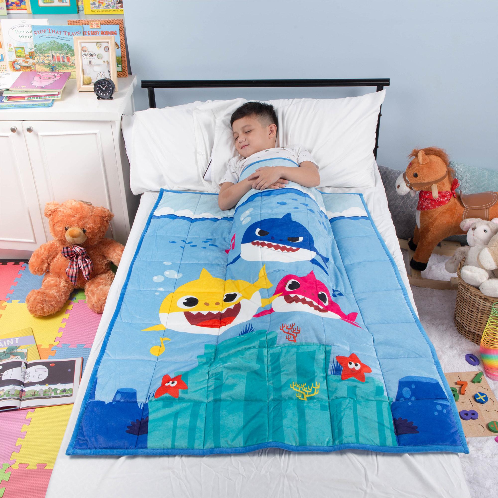kid sleeping underneath a baby shark weighted blanket