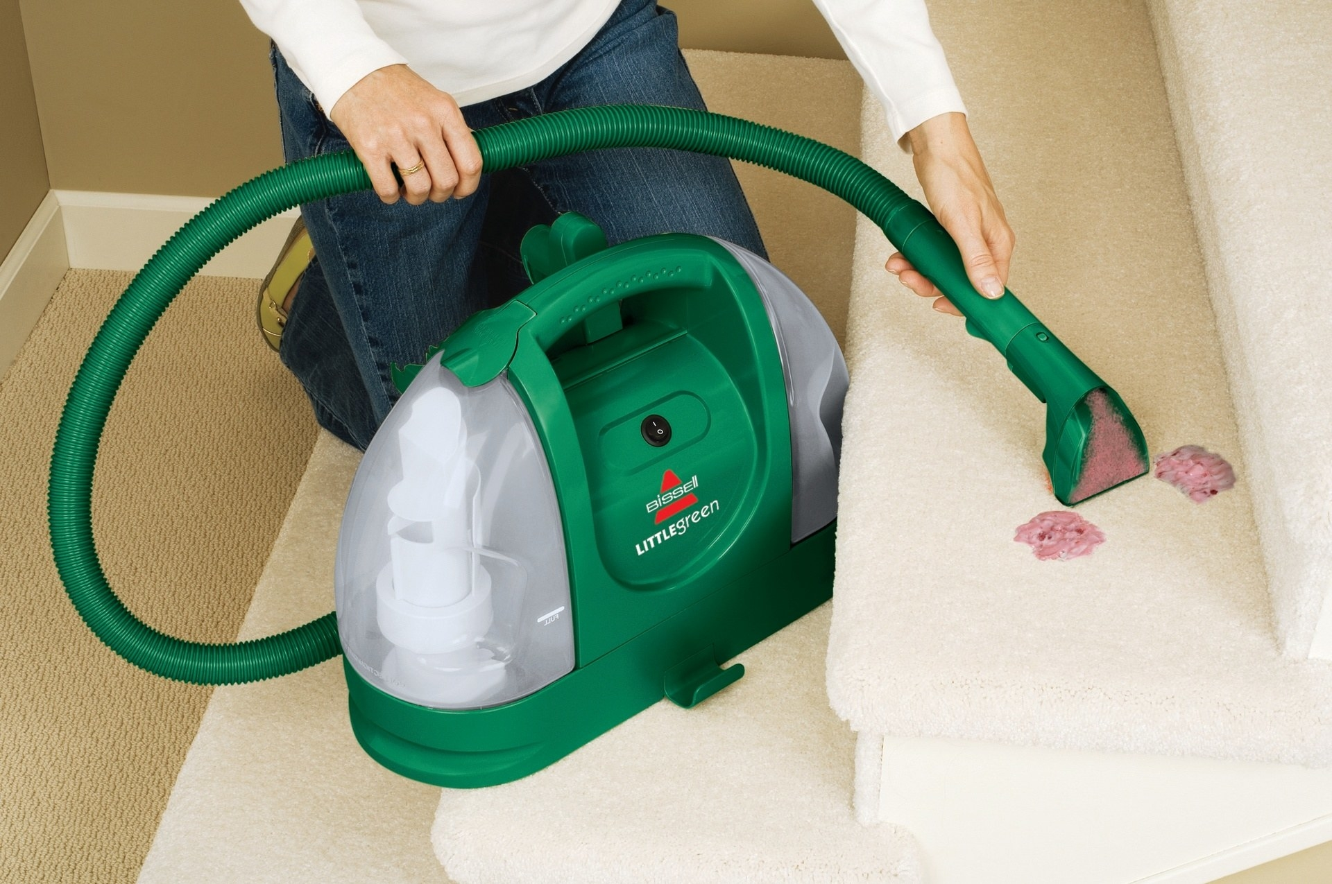 person using a bissell little green machine to clean up a yogurt stain