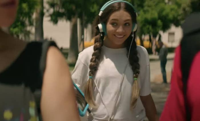 Maddie Ziegler wearing headphones and interacting with two other people