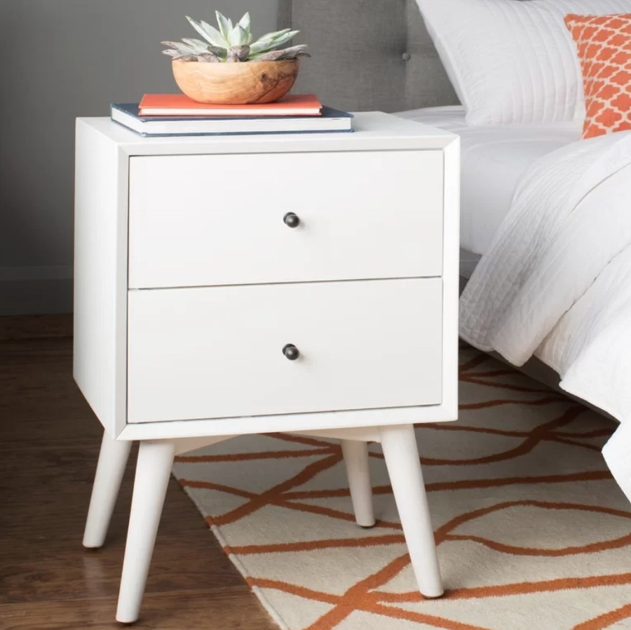 2-drawer white nightstand with books and plant on top
