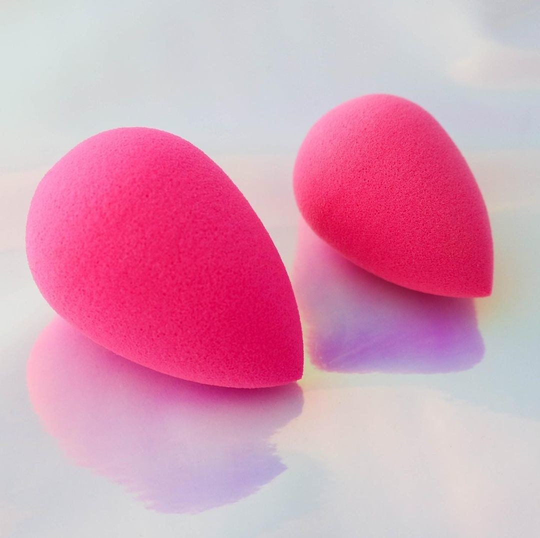 Two small makeup sponges of different sizes on a counter top
