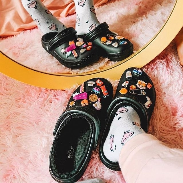 Person in a cozy setting wearing the Crocs with cute additional embellishments