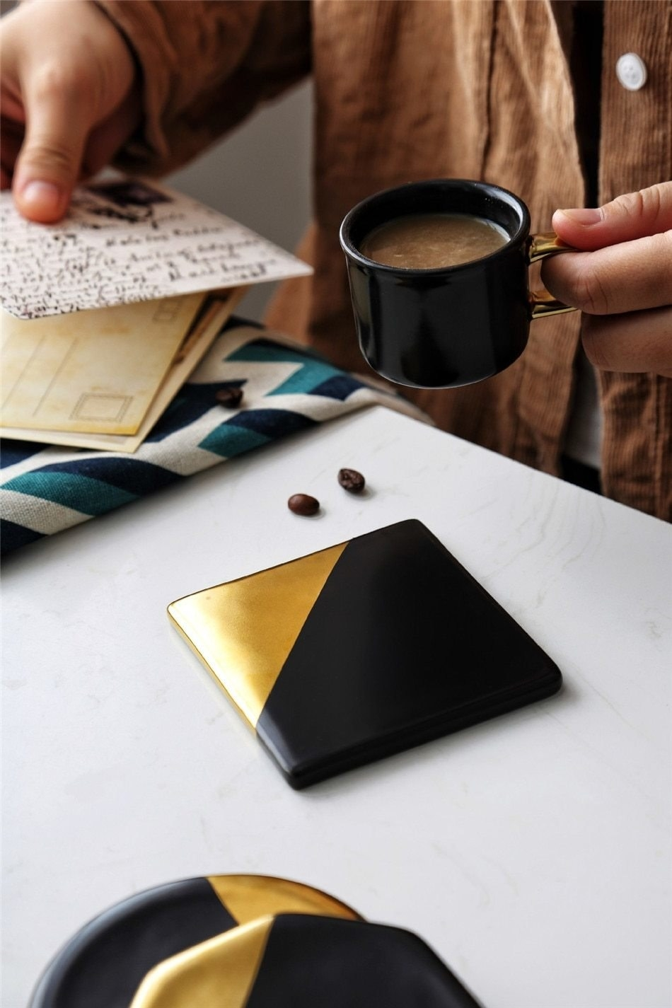 a square black coaster with a gold triangle painted on it