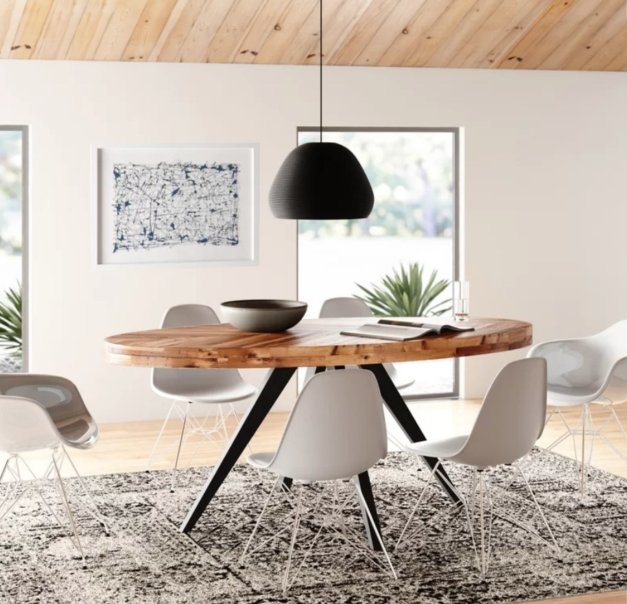 Wooden oval kitchen table with black legs, accompanied by white kitchen chairs