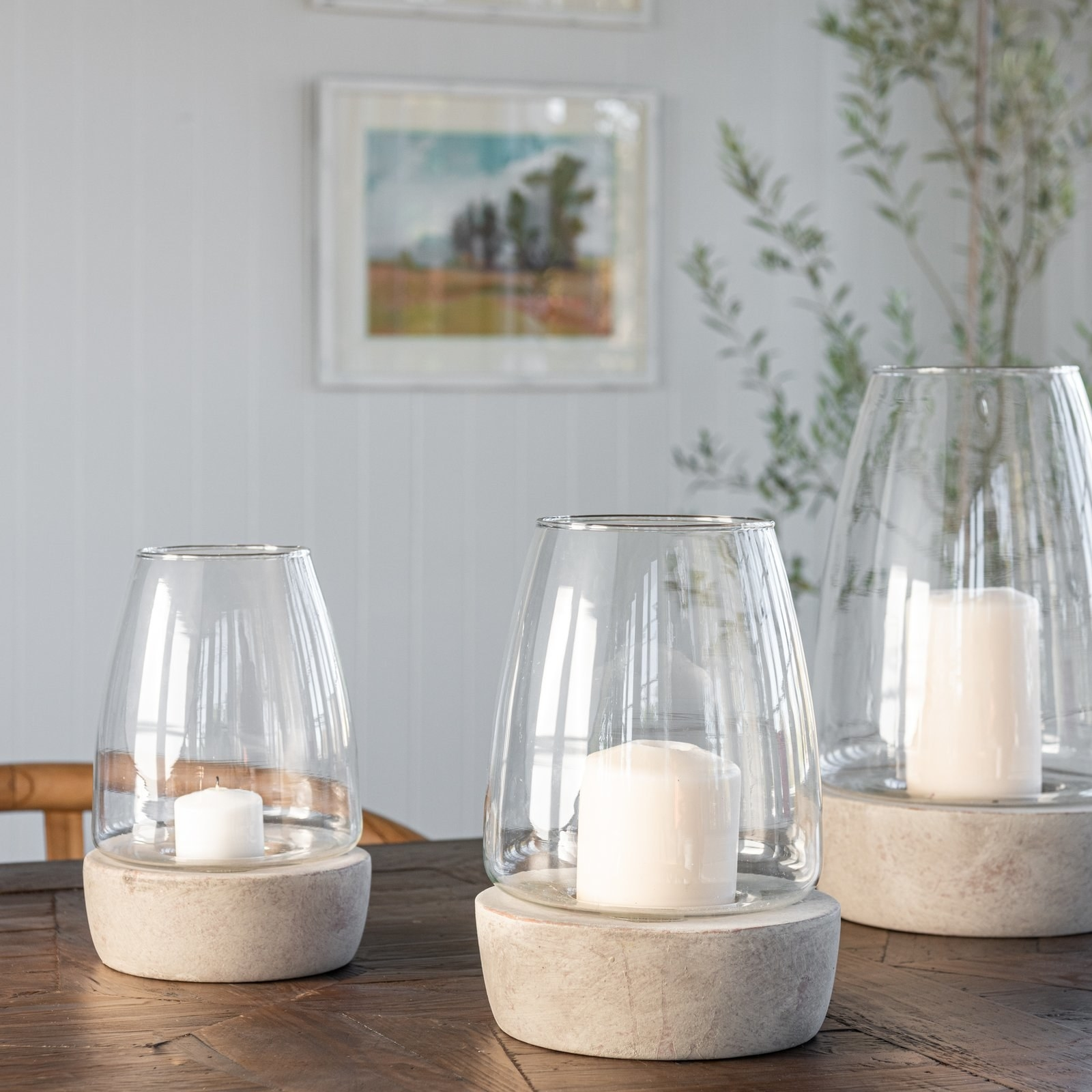 three tapered glass lanterns with a gray terracotta base