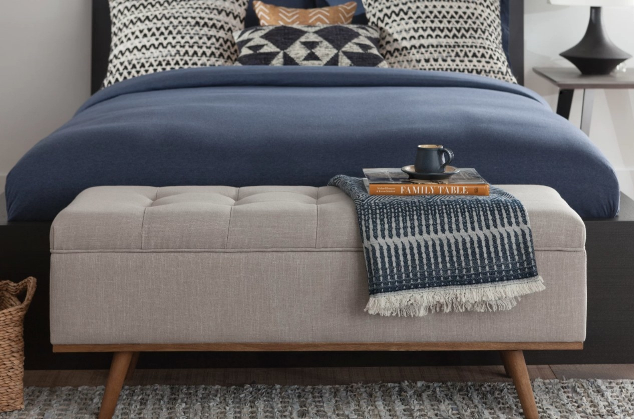 Beige upholstered storage bench with wooden legs at the base of a bed